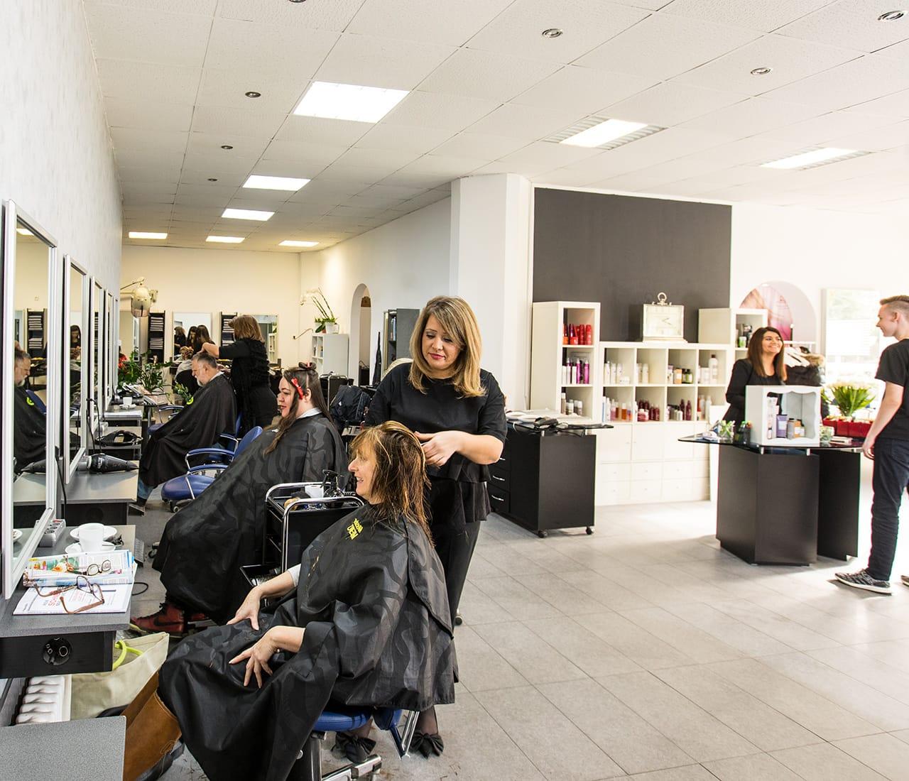 Mitarbeiterin von Memo's Haarstudio beim Färben der Haare einer Kundin