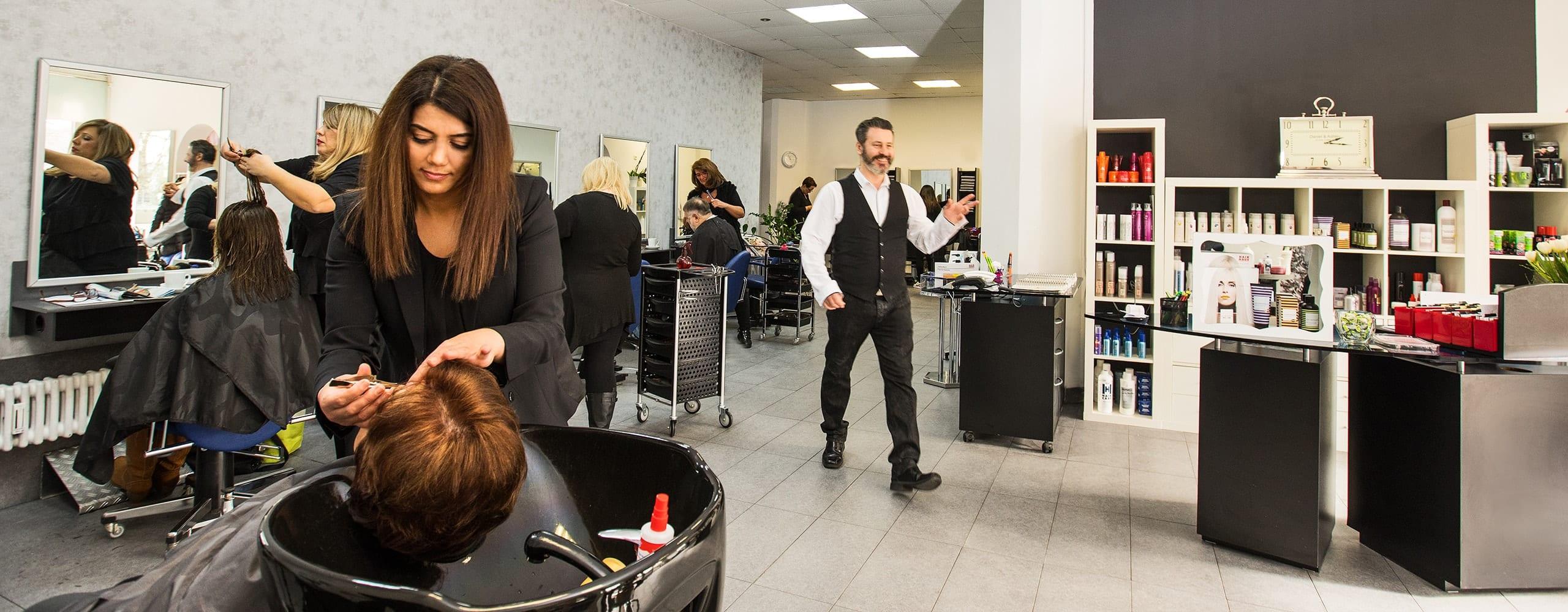 Mitarbeiterin von Memo's Haarstudio am waschen der Haare einer Kundin